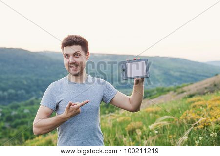 Man Holding An Ebook And Points By Finger And Smiling