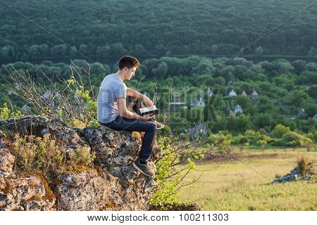 Man Sits On The Edge Of A Cliff And Reading A Book