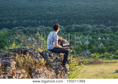 Man Sitting On The Edge Of A Cliff With Book