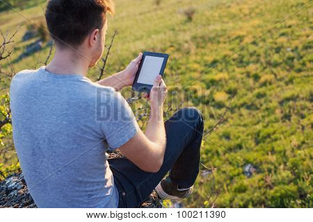 Man Sitting On The Edge Of A Hill And Reading A Ebook
