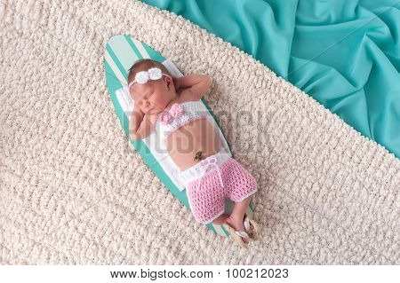 Newborn Baby Girl Sleeping On A Surfboard