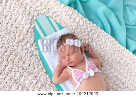 Headshot Of A Newborn Baby Girl Sleeping On A Surfboard