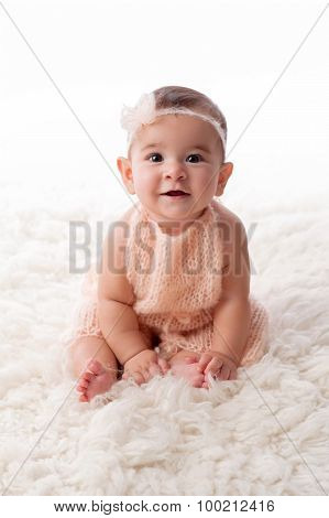 Happy Baby Girl Wearing A Peach Colored, Kintted Mohair Romper
