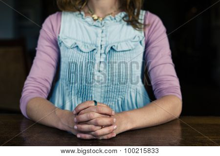 Woman Sitting With Hands Foldded At Table