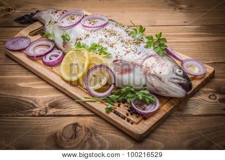 Rainbow trout with fresh spices on the wooden
