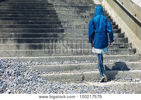 Person In Blue Jacket Walking Up Stairs Outside