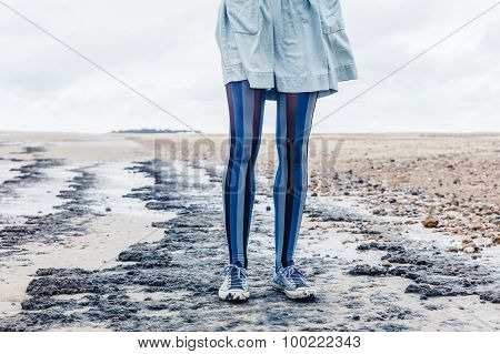 Legs Of Young Woman On Beach
