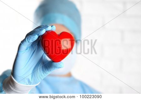 Doctor holding decorative heart on brick wall background