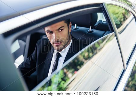 Handsome businessman looking at window in car
