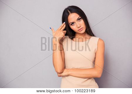 Portrait of a charming woman making gun gesture to her head over gray background