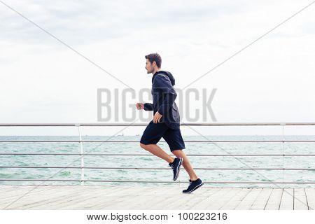 Side view portrait of a sports man running near sea