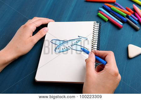 Female hands drawing plane in notebook on wooden table background