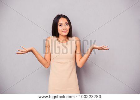 Portrait of a young woman shrugging shoulders over gray background