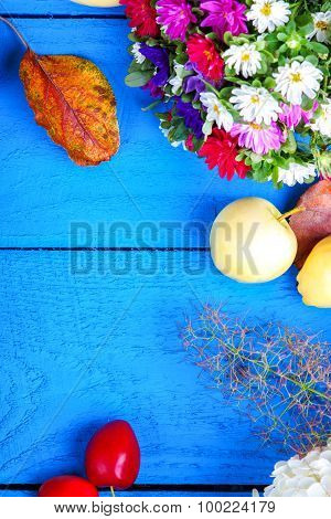 Apples, flowers, leaf litters and plums on a wooden table