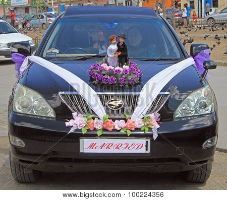 car with bride and her mom stopped on the street in Ulaanbaatar, Mongolia