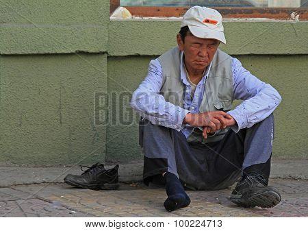 drunk man is sitting on asphalt in Ulaanbaatar