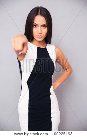 Portrait of a serious woman pointing finger at camera over gray background