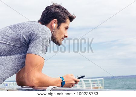 Side view portrait of a sports man standing near sea outdoors