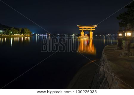 A Ship Passing Under The Famous Orange Shinto Gate Of Miyajima Island Of Hiroshima Prefecture, Japan