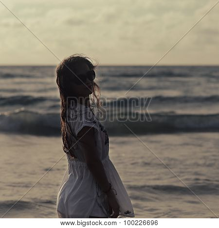 Beautiful Woman In Summer Dress Standing In Ocean On Sunset Eveing Background