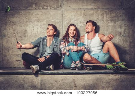 Cheerful friends with with skateboard taking selfie outdoors