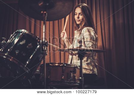 Young cheerful girl behind drums on a rehearsal