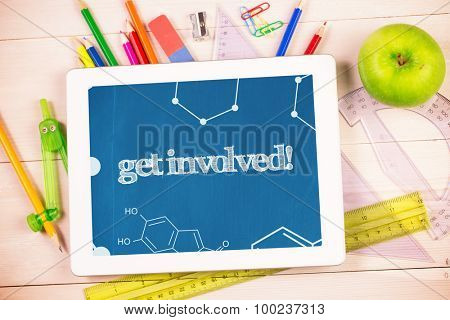 The word get involved! and science graphic against students desk with tablet pc