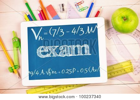 The word exam and maths equation against students desk with tablet pc