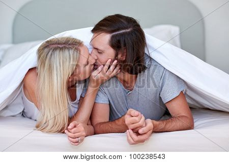 romantic young affectionate married couple kissing on bed under duvet at home