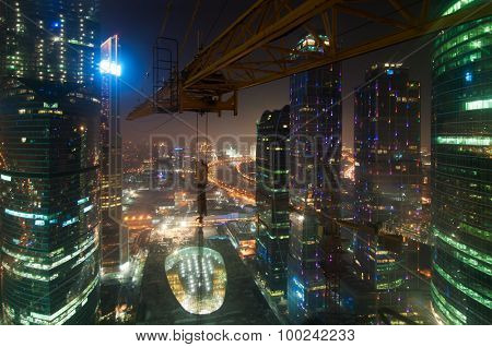 MOSCOW, RUSSIA - FEB 22, 2015: Crane, shopping complex Central Core among towers of business complex Moscow City at night. Investments in project Central Core - 300 million dollars