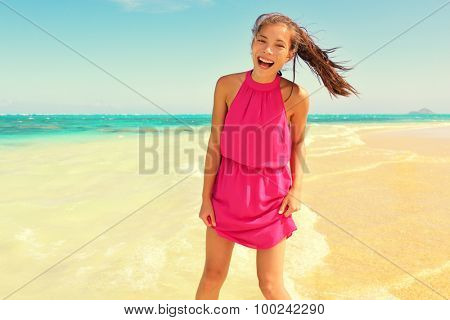 Portrait of happy young woman in pink dress standing at beach. Beautiful mixed race Asian / Caucasian female is enjoying her summer vacation. Carefree woman is laughing while standing on shore.