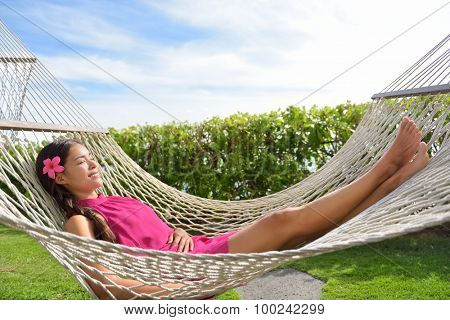 Full length of happy relaxed young woman lying on hammock. Smiling mixed race Asian / Caucasian female is in dress. She is enjoying sunlight in park.