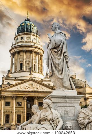 Beautiful squares in Berlin, the Gendarmenmarkt, marble statue of German poet Friedrich Schiller at sunset
