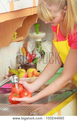 Woman Washing Fresh Vegetables In Kitchen