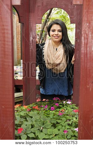 A pretty teen girl viewed through the openings of a flower-filled redwood gazebo.