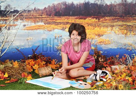 A pretty young teen in the fall  looking up at the viewer as she begins to paint the scene around her as she sits at the edge of pond.