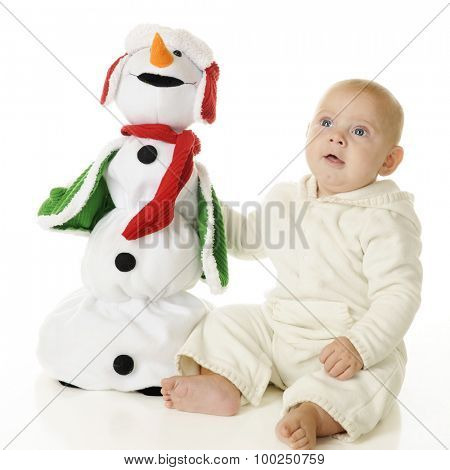 An adorable baby boy happily sitting with his toy Christmas snowman.  On a white background.