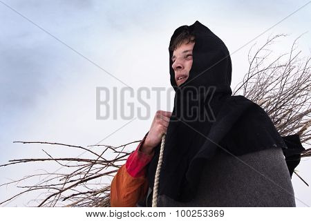 Medieval Peasant With A Firewood  Bundle Sitting In The Snow