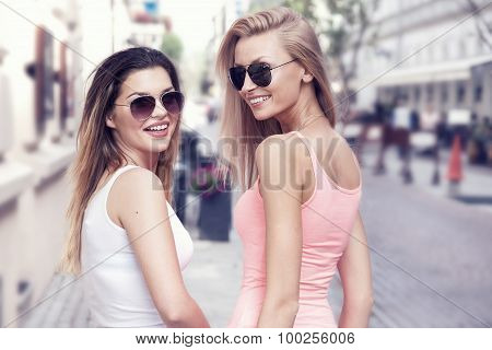 Two Young Smiling Girls Walking In The City.