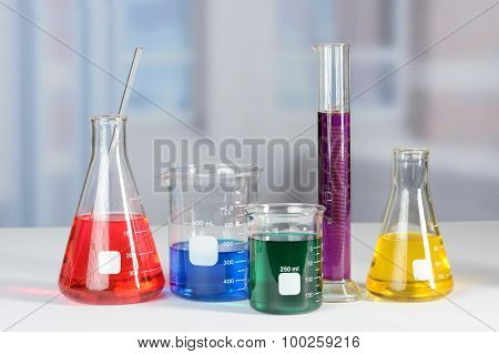 Laboratory flasks and beakers with liquids of different colors on lab table