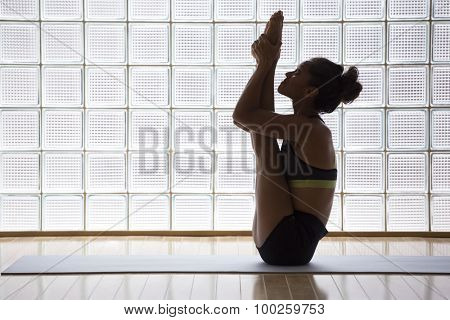 Young woman practicing in a yoga studio indoors. This asana is a very advanced verion of Urdhva Mukha Paschimottanasana.