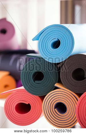 Pile of yoga mats rolled in a yoga studio
