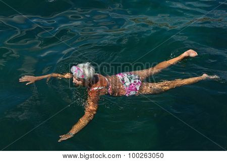 Aged Woman Is Swimming With Goggles In The Sea.