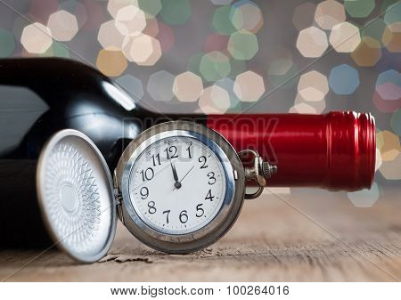 Clock And Red Wine Against Holiday Lights
