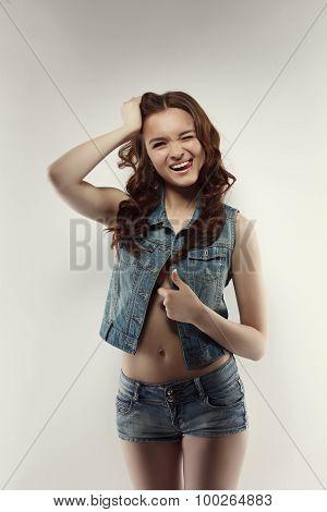 Studio shot of funny teen model winks at camera