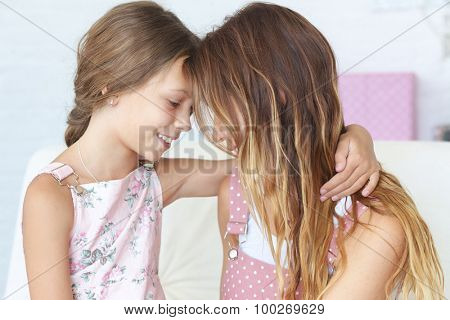 Mother with her 8 years old daughter hugging on a sofa at home