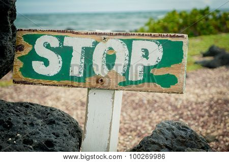 old wooden stop sign warning about a protected beach area in galapagos islands
