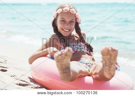 9 years old girl dressed in fashion floral swimsuit playing with inflatable ring at the beach in sunlight