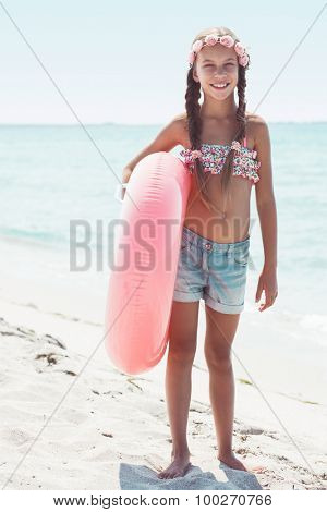 9 years old girl dressed in fashion floral swimsuit and denim shorts posing with inflatable ring at the beach in sunlight