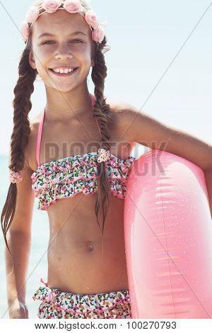 9 years old girl dressed in fashion floral swimsuit posing with inflatable ring at the beach in sunlight